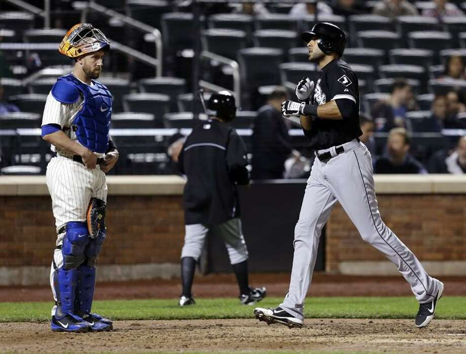 New York Mets catcher John Buck, left, watches as Chicago White Sox's Alex Rios crosses home plate after hitting a solo home run during the ninth inning of a baseball game at Citi Field, Wednesday, May 8, 2013, in New York. The White Sox won 6-3. (AP Photo/Seth Wenig) Photo: AP / AP