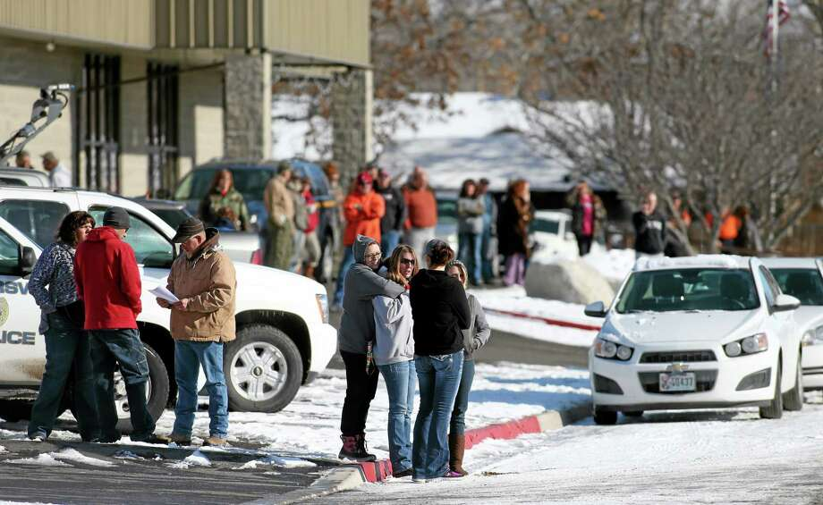 A crowd gathers outside the command post in Lovelock, Nev., on Tuesday, Dec. 10, 2013, awaiting the return of a group of six people who survived two days in the frigid mountains east of Reno. The two adults and four children are being treated at the local hospital. (AP Photo/Cathleen Allison) Photo: AP / FR70203 AP