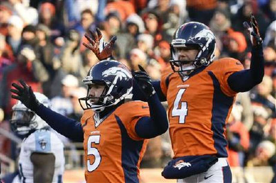 Denver Broncos kicker Matt Prater, left, celebrates a 64-yard field goal with Britton Colquitt during the first half of an NFL football game against the Tennessee Titans during the first half of an NFL football game on Sunday, Dec. 8, 2013, in Denver. Photo: AP / FR42408 AP