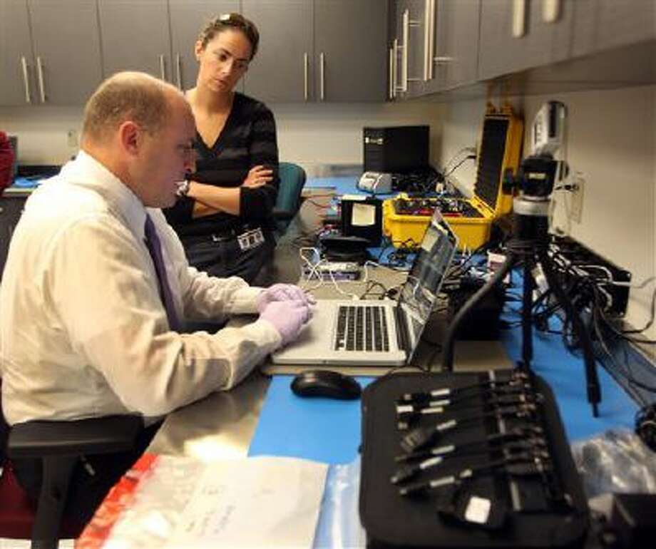 Computer examiner Sgt. Rick Nelson, of the Peterborough, N.H., police department works on locating information on a hard drive with Det. Caitlin Rebe of the Hookset, N.H. police department at the state's Internet Crimes Against Children unit. Nelson and other computer technicians from across the state are working to fight the escalating trafficking in child sex abuse images through the internet. Meanwhile, a Pennsylvania proposal calls for making 611 a hotline for reporting child abuse. Photo: AP / AP