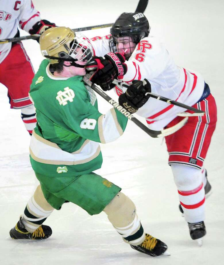William Vizzo, left, of Notre Dame of West Haven is cross-checked in the head by Kevin Brown, right, of Fairfield Prep third period in Bridgeport last month. Prep and Notre Dame remain the top two teams in the latest poll. Photo by Arnold Gold/New Haven Register