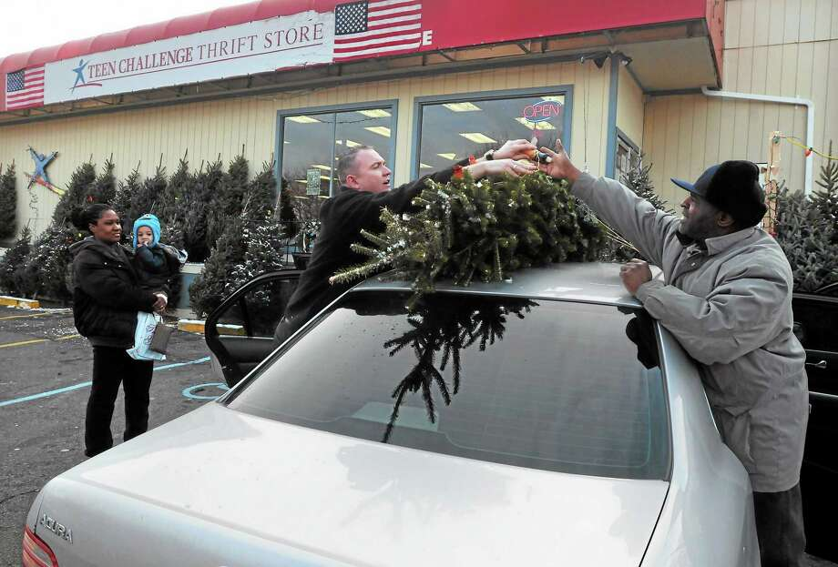 (Mara Lavitt — New Haven Register)   Lakeitha Horne with her grandson Jahri Goodman, age 2, watch as Teen Challenge CT store manager Michael Hayes-Moore and Jerry Norfleet tie Horne's Christmas tree on her car. All are of New Haven. Photo: Journal Register Co. / Mara Lavitt