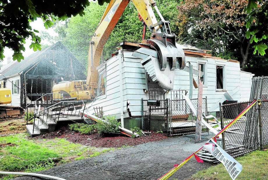 Arnold Gold — RegisterOne of two houses destroyed by a plane crash on Charter Oak Ave. in East Haven is demolished on 8/22/2013. In the background is the other house. Photo: Journal Register Co.