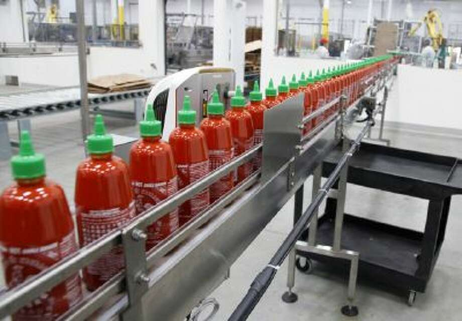 Sriracha chili sauce moves along a production line during at the Huy Fong Foods factory in Irwindale, Calif., on Tuesday, Oct 29, 2013.
