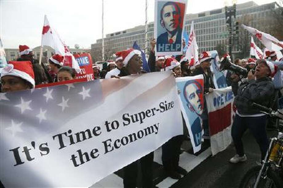 Activists, holding posters of President Barack Obama, momentarily block Independence Avenue in Washington on Dec. 5 as they protest the minimum wage outside a McDonald's restaurant at the Smithsonian's National Air and Space Museum in Washington. Photo: AP / AP