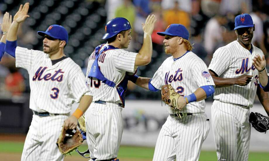 New York Mets catcher Travis d'Arnaud (15) celebrates with teammates Omar Quintanilla (3), Justin Turner (2) and LaTroy Hawkins, right, after their 5-3 win in a baseball game against the Atlanta Braves Tuesday, Aug. 20, 2013, in New York. (AP Photo/Frank Franklin II) Photo: AP / AP