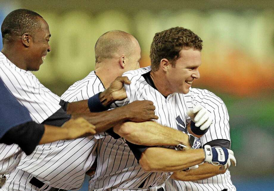 New York Yankees Alfonso Soriano, left, and Brett Gardner celebrate with Jayson Nix, right,  after he hit the game-winning RBI single to lift the Yankees to a 3-2 win over the Toronto Blue Jays in the second baseball game of a doubleheader at Yankee Stadium, Tuesday, Aug. 20, 2013, in New York. (AP Photo/Kathy Willens) Photo: AP / AP