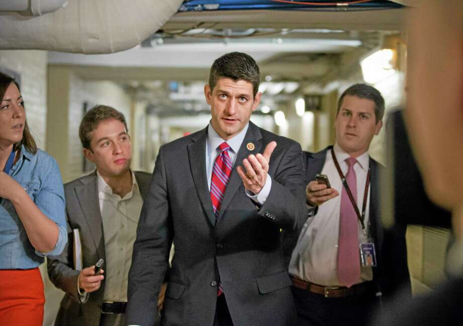 Walking through a basement corridor on Capitol Hill in Washington, Wednesday, House Budget Committee Chairman Rep. Paul Ryan, R-Wis., is pursued by reporters on the morning after a budget deal was worked out between Ryan and Senate Budget Committee Chairwoman Sen. Patty Murray, D-Wash. Photo: J. Scott Applewhite — The Associated Press   / AP