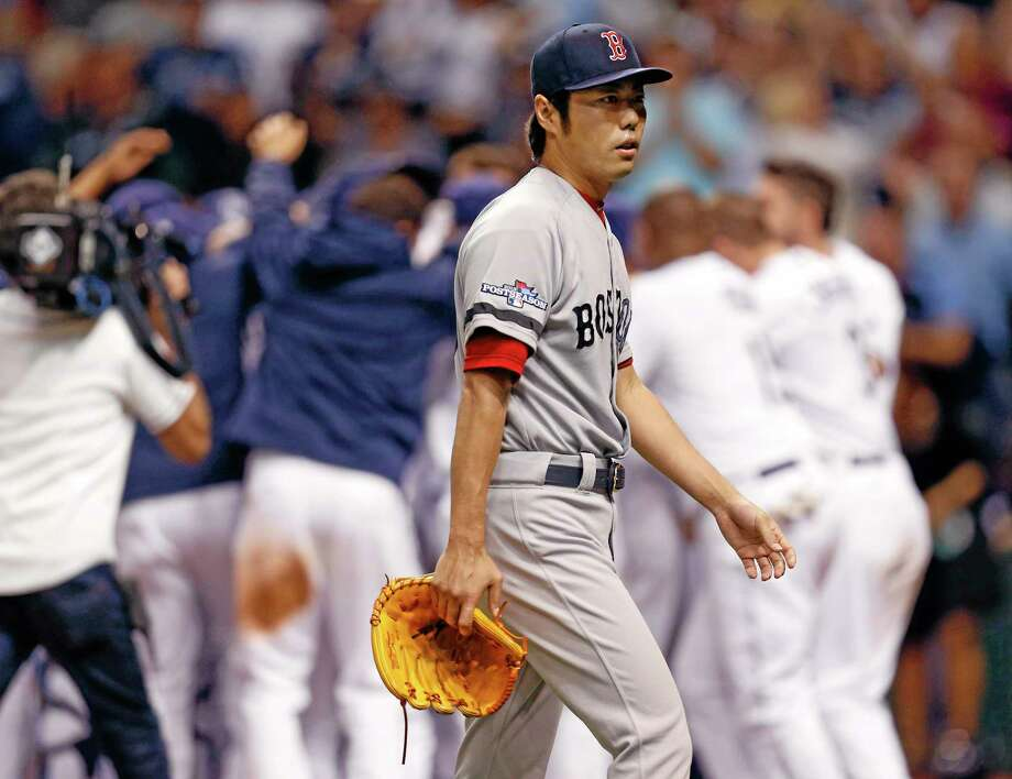Red Sox relief pitcher Koji Uehara walks away as the Rays celebrate the game-winning home run by Jose Lobaton in the ninth inning Monday. Photo: Mike Carlson — The Associated Press   / FR155492 AP
