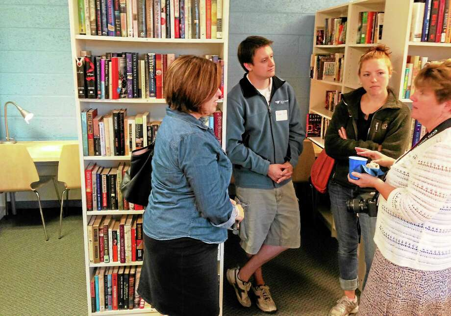 With one of the study nooks at left and another behind them, Business Manager Eileen Davis, right, chats with nonprofit adviser Heather Calabrese, Ryan Davis and Kerilyn Peck at the open house. Photo: Journal Register Co.