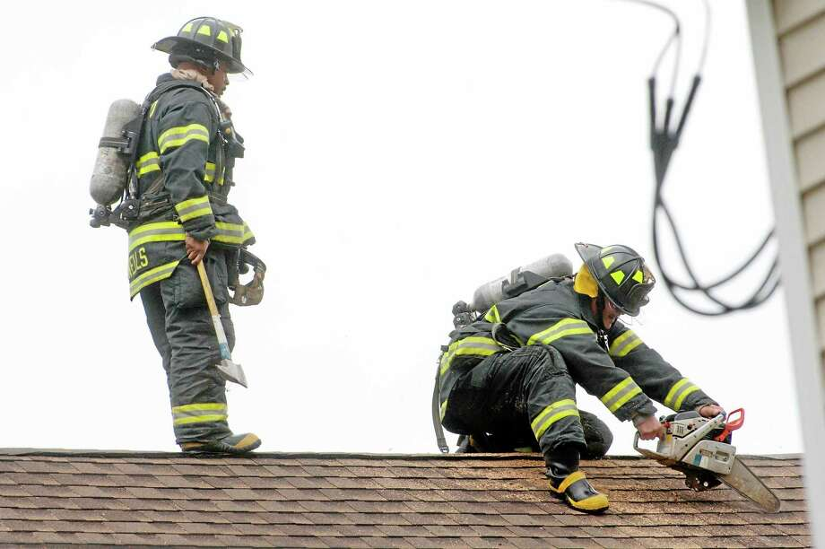 vmWilliams - New Haven RegisterNew Haven firefighters saw a hole in the roof of a house at 175 Hallock St in hopes of containing a fire that occurred there October 7, 2013. Photo: Journal Register Co.