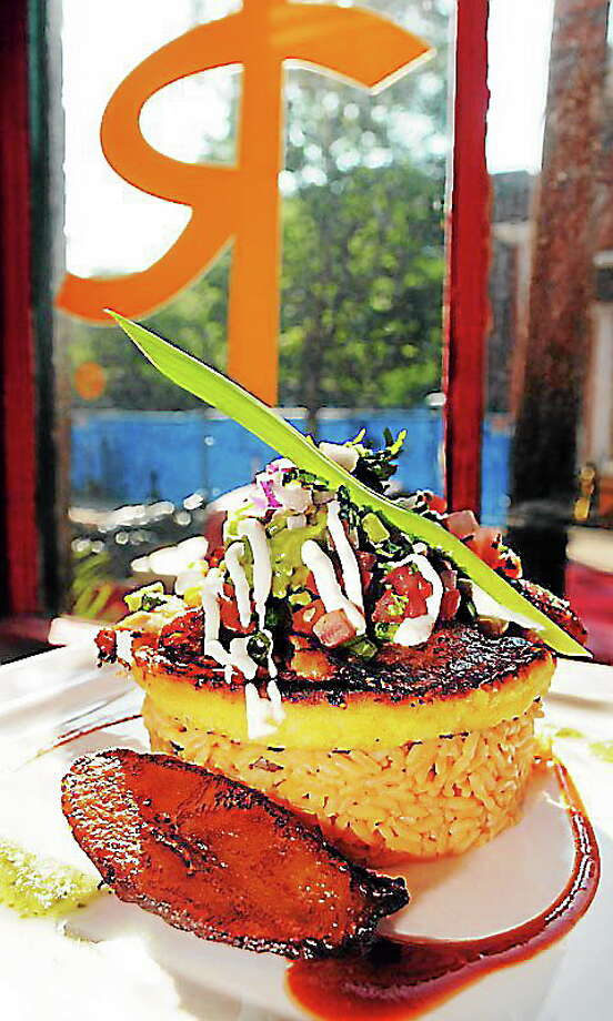 Mara Lavitt — Register August 12, 2013 Rubamba restaurant, New Haven. Pescado Arepa: ancho chile-rubbed tilapia and grilled sweet-corn cake with mozzarella, rice and gandules, plantains, vegetable ragout, pico de gallo, guacamole and sour cream. Photo: Journal Register Co.