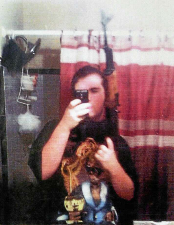 In this undated photo provided by the Dekalb County Police Department, Michael Brandon Hill poses with an AK 47-style rifle that authorities believed is the one he had when he was arrested at a Decatur, Ga., elementary school on Tuesday, Aug. 20, 2013. Investigators say that Hill took the photo and packed up nearly 500 rounds of ammunition, then headed to the Ronald E. McNair Discovery Learning Academy. No one was injured, but the suspect exchanged gunfire with police. (AP Photo/Dekalb County Police Department) Photo: AP / Dekalb County Police Department