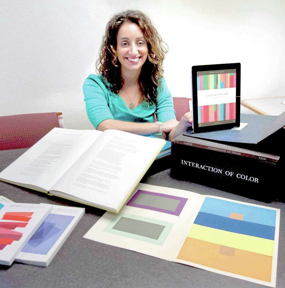 "Michelle Komie, senior editor of Art and Architecture at Yale University Press poses for a photograph with multiple versions of late Yale Prof. Josef Albers' book ""Interaction of Color"" including the new app version. Vern Williams/New Haven Register. August 16, 2013. Photo: Journal Register Co."