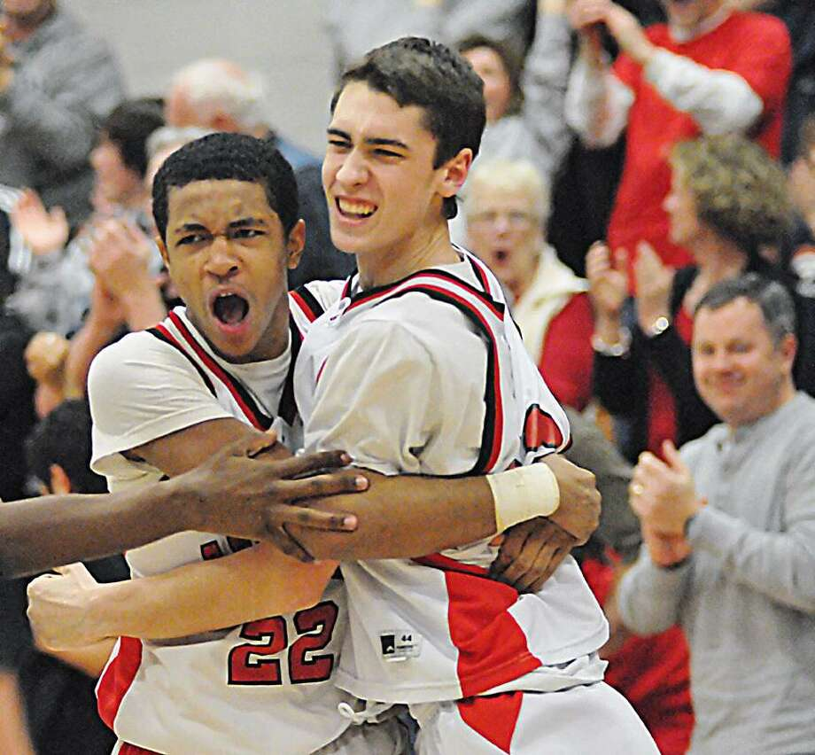 Catherine Avalone/The Middletown Press Cromwell senior forward Kevin Francis (23) at far right celebrates with junior point guard Matt Turkington following Francis' buzzer shot against Immaculate, winning the game 57-55 in Cromwell Monday night in the CIAC First Round State Basketball Tournament. / TheMiddletownPress