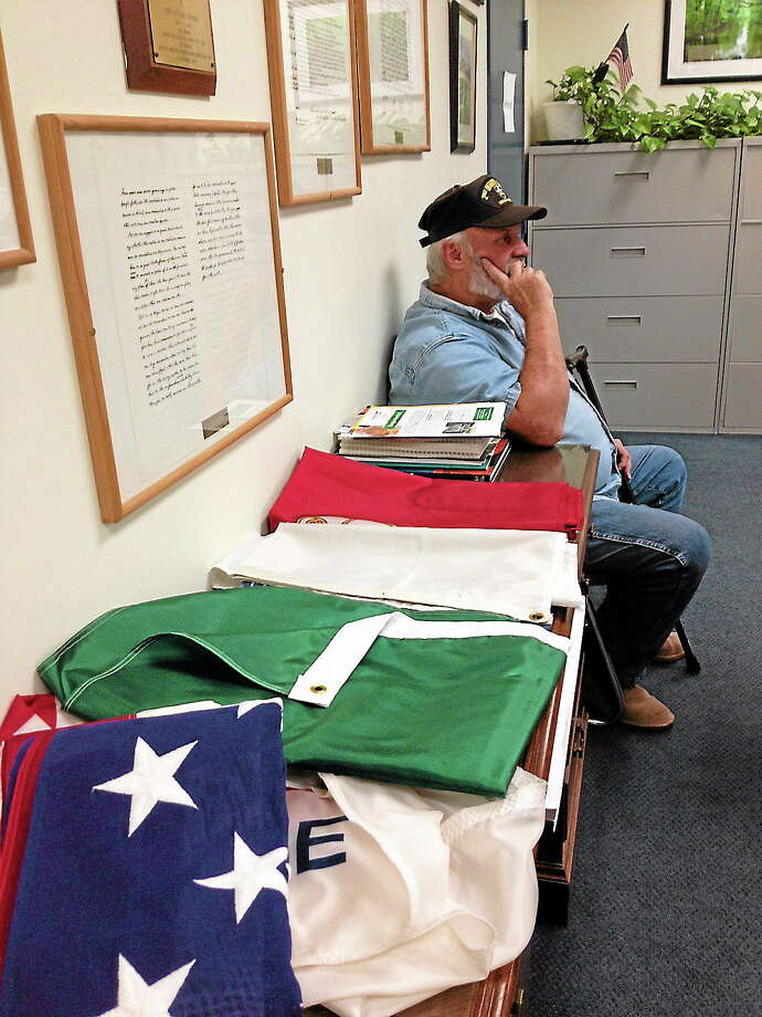 Fred McCarthy sits beside the Rotunda's old flags, currently unequipped for the new flag poles at Memorial Town Hall. (Photo by Michael Bellmore/New Haven Register) Photo: Journal Register Co.