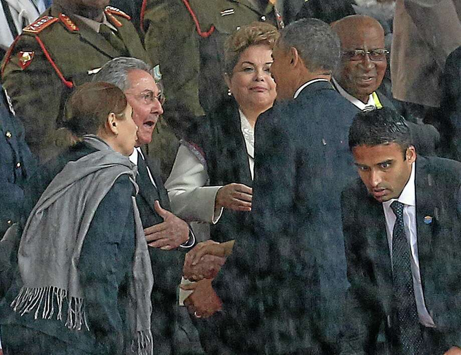US President Barack Obama shakes hands with Cuban President Raul Castro as Brazilian President Dilma Rouseff  looks on at centre at the FNB Stadium in Soweto, South Africa, in the rain for a memorial service for former South African President Nelson Mandela, Tuesday Dec. 10, 2013. The handshake between the leaders of the two Cold War enemies came during a ceremony that's focused on Mandela's legacy of reconciliation. Hundreds of foreign dignitaries and world heads of states gather Tuesday with thousands of South African people to celebrate the life, and mark the death, of Nelson Mandela who has became a global symbol of reconciliation. (AP Photo) SOUTH AFRICA OUT Photo: AP / AP