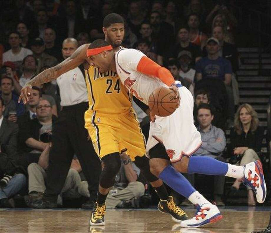 New York Knicks' Carmelo Anthony drives past Indiana Pacers' Paul George during the first half of Game 2 of their NBA basketball playoff series in the Eastern Conference semifinals  Tuesday, May 7, 2013, at Madison Square Garden in New York. The Knicks won 105-79. (AP Photo/Mary Altaffer) Photo: AP / AP