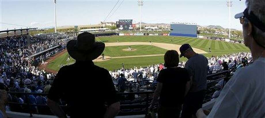 Fans stand during the seventh inning stretch in an exhibition spring training baseball game between the Seattle Mariners and the Colorado Rockies, Monday, March 4, 2013, in Peoria, Ariz. (AP Photo/Charlie Riedel) Photo: AP / AP