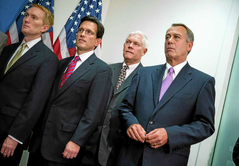 House Speaker John Boehner of Ohio, right, joined by members of the Republican Caucus, watches during a news conference on Capitol Hill in Washington, Friday, Oct. 4, 2013. From left are, Rep. James Lankford, R-Okla., House Majority Leader Eric Cantor of Va., Rep. Pete Sessions, R-Texas, and Boehner. Boehner is struggling between Democrats that control the Senate and GOP conservatives in his caucus who insist any funding legislation must also kill or delay the nation's new health care law. Added pressure came from President Barack Obama who pointedly blamed Boehner on Thursday for keeping federal agencies closed. (AP Photo/J. Scott Applewhite) Photo: AP / AP