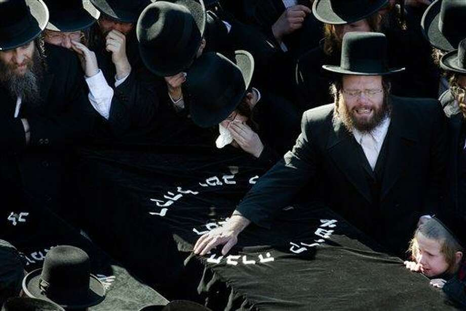 Members of the Satmar Orthodox Jewish community grieve over the coffins at the funeral for two expectant parents who were killed in a car accident, Sunday, March 3, 2013, in the Brooklyn borough of New York. A driver struck the car early Sunday morning, killing both parents while their baby, who was born prematurely, survived and is in critical condition. (AP Photo/John Minchillo) Photo: AP / FR170537 AP