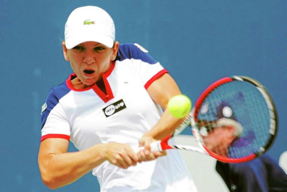 Simona Halep hits a shot to Daniela Hantuchova at the New Haven Open Monday. Aug. 18, 2013. (Bob Child Photo) Photo: Journal Register Co.
