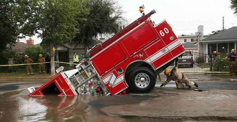 A Los Angeles fireman looks under a fire truck stuck in a sinkhole in the Valley Village neighborhood of Los Angeles Tuesday, Sept. 8, 2009. Four firefighters escaped injury early Tuesday after their fire engine sunk into a large hole caused by a burst water main in the San Fernando Valley, authorities said.  (AP Photo/Nick Ut) Photo: ASSOCIATED PRESS / AP2009