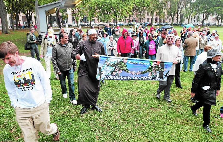 (Arnold Gold — New Haven Register)  Bruce Barrett (far left), founder ofg IWagePeace.Org, and walkers begin the I Wage Peace Walk on the New Haven Green on 10/6/2013. Photo: Journal Register Co.