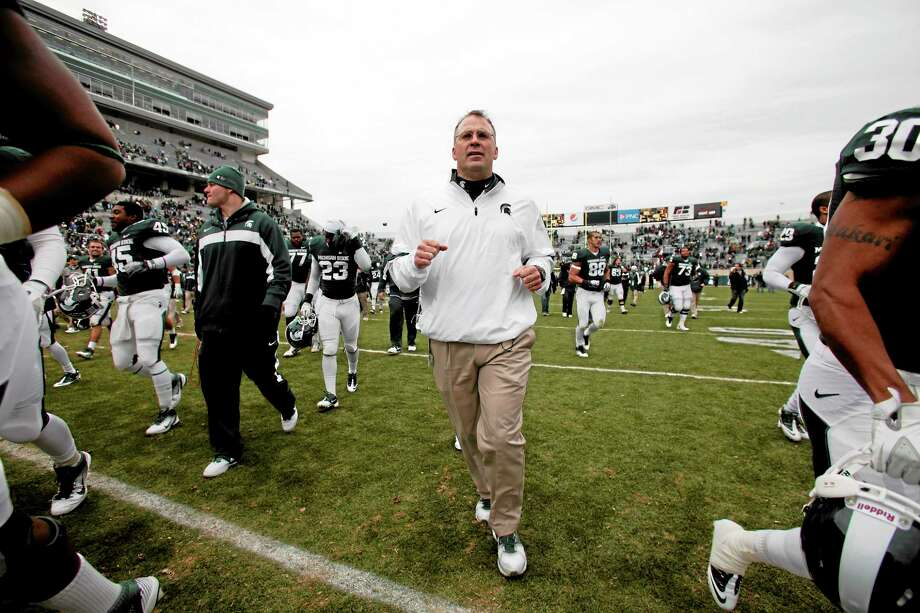 Michigan State head coach Mark Dantonio confirmed UConn has requested to speak with Spartans defensive coordinator Pat Narduzzi, center, about the Huskies' head coaching position. Photo: Al Goldis — The Associated Press   / FR11125 AP