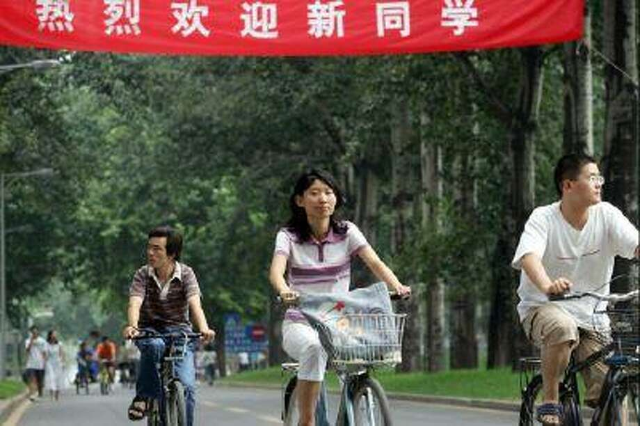 Chinese university students cycle on the campus of Tsinghua University in Beijing.