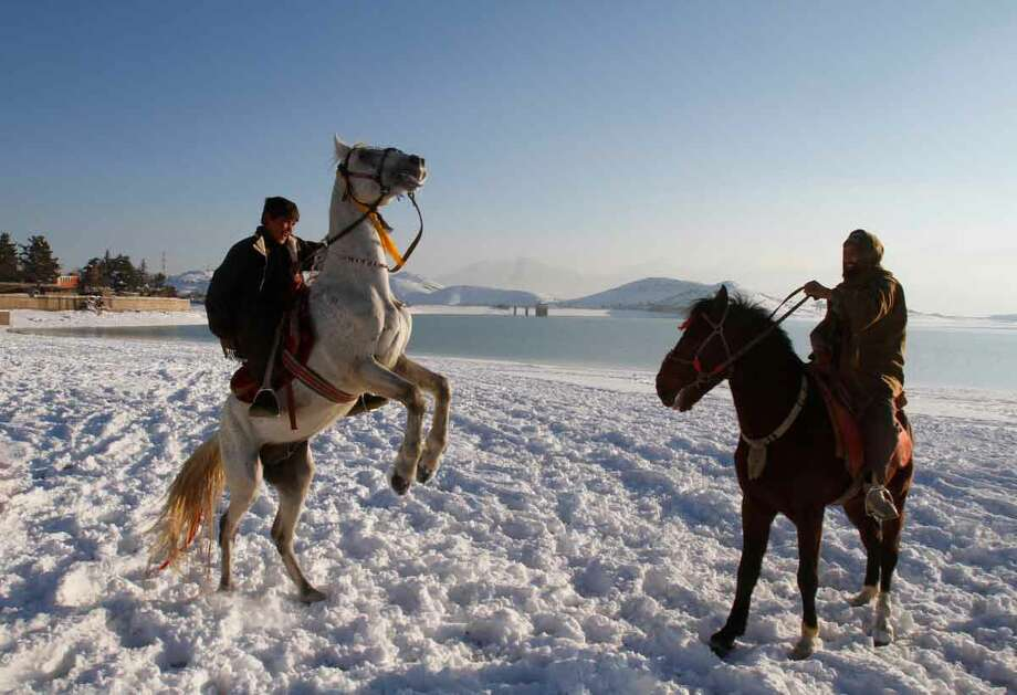 Afghan men ride horses in the snow on the shores of Lake Qargha in Kabul, Afghanistan, Tuesday, Jan, 1, 2013. (AP Photo/Ahmad Jamshid) Photo: ASSOCIATED PRESS / AP2013