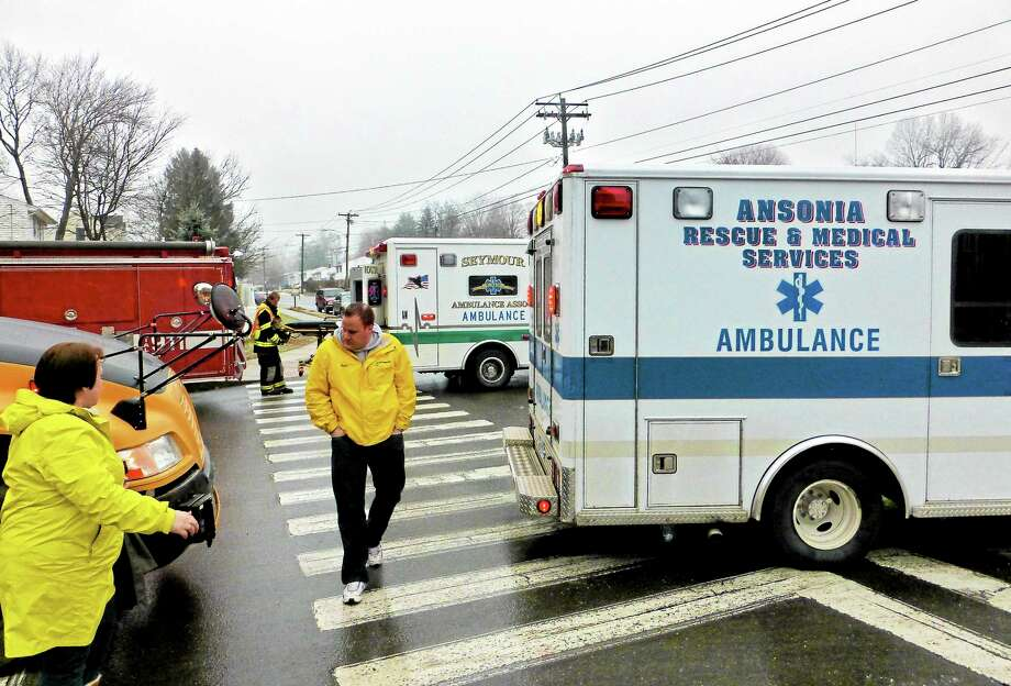 Steve Gardiner from All Star Transportation Co., center, surveys a school bus that was hit at the corner of Benz and Hill streets in Ansonia Monday. Photo: Patricia Villers — New Haven Register