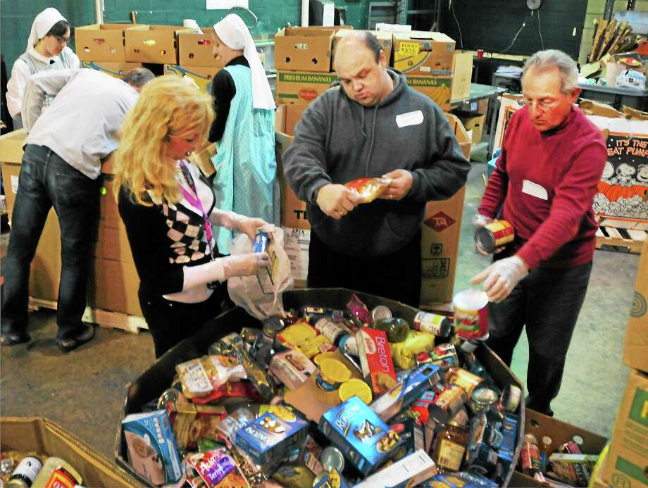 (Peter Hvizdak — New Haven Register)Volunteers Kim Lucas of West Haven,  Mark Dalton of  West Haven and Al DeFilippo of Branford (left to right facing camera) sort through food drive donations in the salvage room Tuesday, November 19, 2013 at the Connecticut Food Bank headquarters in  East Haven, Conn. Photo: New Haven Register / ©Peter Hvizdak /  New Haven Register