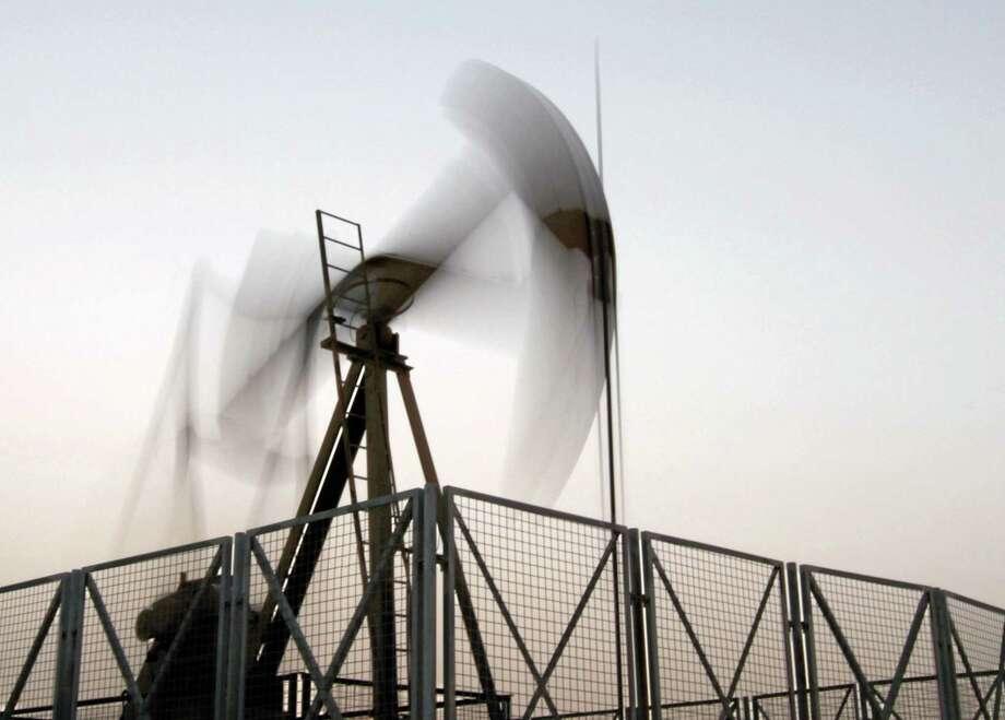Hasan Jamali — The Associated Press file photo  An oil pump jack works at sunset in the desert oil fields of Sakhir, Bahrain, in June. Photo: AP / AP