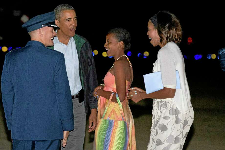 President Barack Obama, second from left, Sasha Obama, and first lady Michelle Obama, are greeted as they exit Air Force One on arrival at Andrews Air Force Base, Md., on Sunday Aug. 18, 2013, after a family vacation on the island of Martha's Vineyard. Also with them was Malia Obama, not pictured. (AP Photo/Jacquelyn Martin) Photo: AP / AP