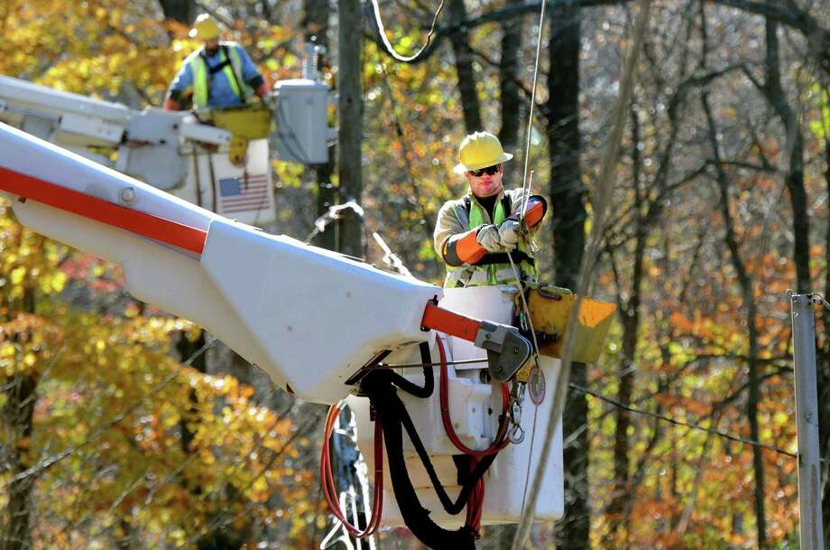 Green Mountain Power (Vermont) linemen Adam Eisel left and Tom Brigan right work to get three houses on Featherbed Lane in Branford back up and running on power. Mara Lavitt/New Haven Register11/3/12