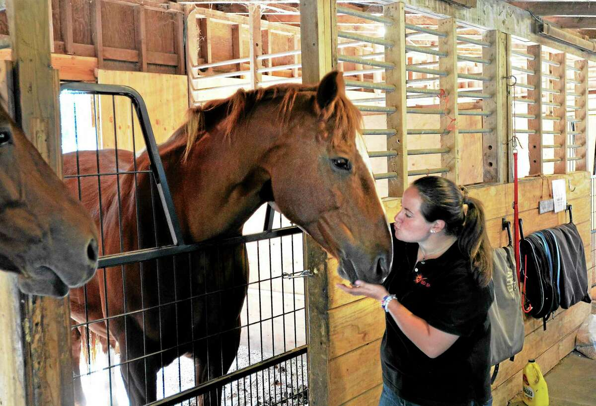 Niki Cogliano, equine specialist at Red Skye Farm, gives some extra attention to Brigitta, one of the horses used for therapy.