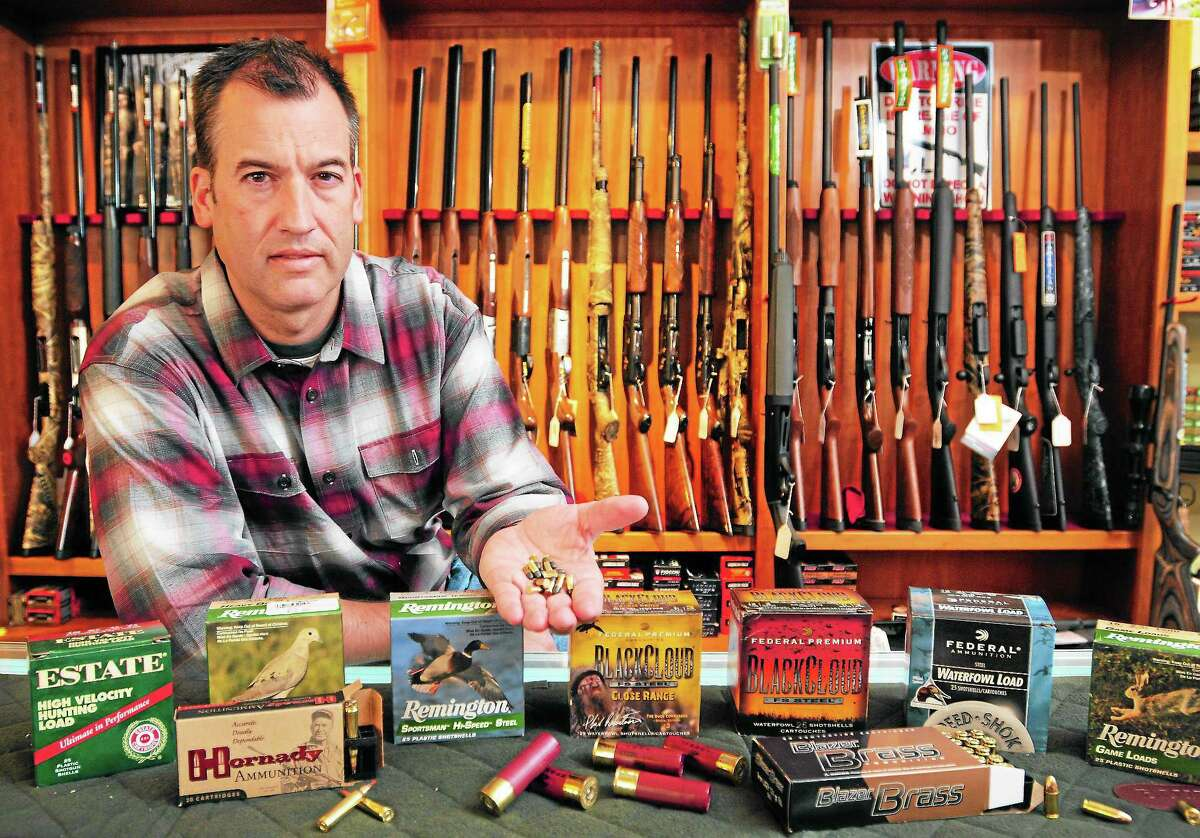 Mike Higgins, co-owner of TGS Outdoors in Branford, shows some rimfire, rifle, shotgun and centerfire pistol ammunition at his store Thursday.