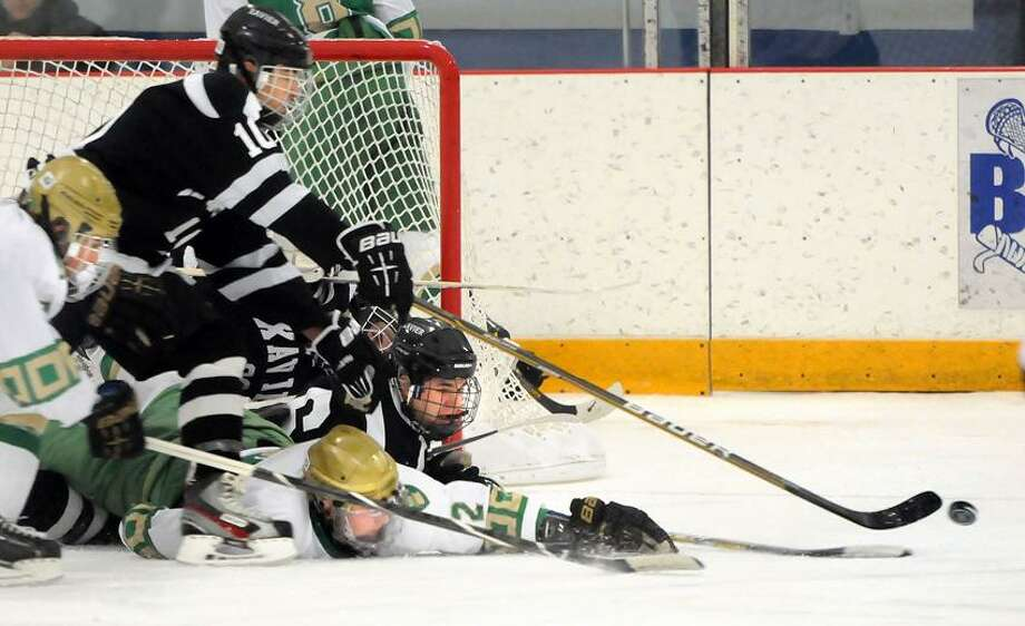 Reaching for that puck includes Notre Dame-West Haven's Greg Zullo and Lou Iannotti, and Xavier's Andrew Meoli, Evan Lindquist, and goalie Shane Baldwin on Monday. Both Notre dame and Xavier won games on Wednesday. Mara Lavitt/New Haven Register.  12/31/12