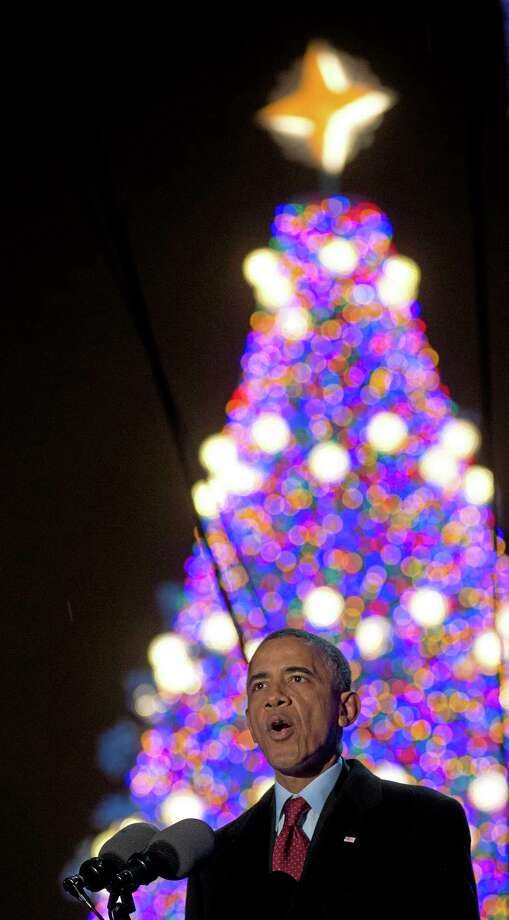 President Barack Obama, speaks as the National Christmas Tree glows behind him during the 2013 National Christmas Tree Lighting ceremony at the Ellipse near the White House in Washington, Friday, Dec. 6, 2013. (AP Photo/Carolyn Kaster) Photo: AP / AP