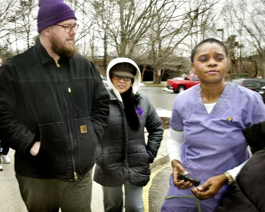 MILFORD--After pinning a  Service Employees International Union button to her uniform, Certified Nursing Assistant, Solange Ngandu (R) prepares to go to work at west River Health Care Center. She, and other returning workers, were escorted by SEIU members including Jesse --, and Rose Davila.    Melanie Stengel/Register