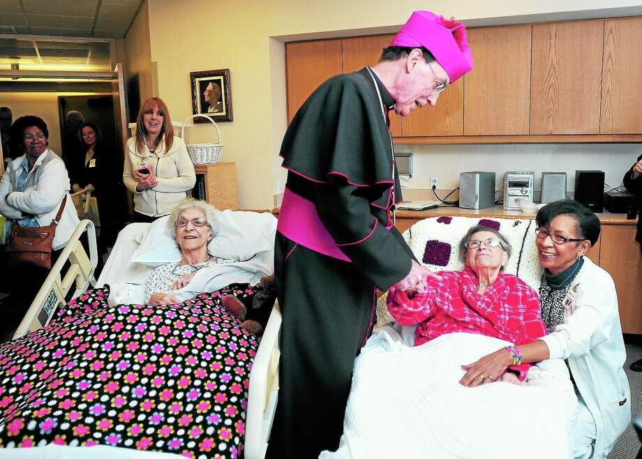 (Arnold Gold — New Haven Register)  Archbishop Henry J. Mansell, center, meets with Doris Kerwin. right, and CNA Coordinator Brenda Cowan-Bogle, far right, at the Connecticut Hospice in Branford on 12/9/2013.  At left is Marie-Natalie Carletti. Correction: An earlier version of this caption misidentified Kerwin and Cowan-Bogle. Photo: Journal Register Co.