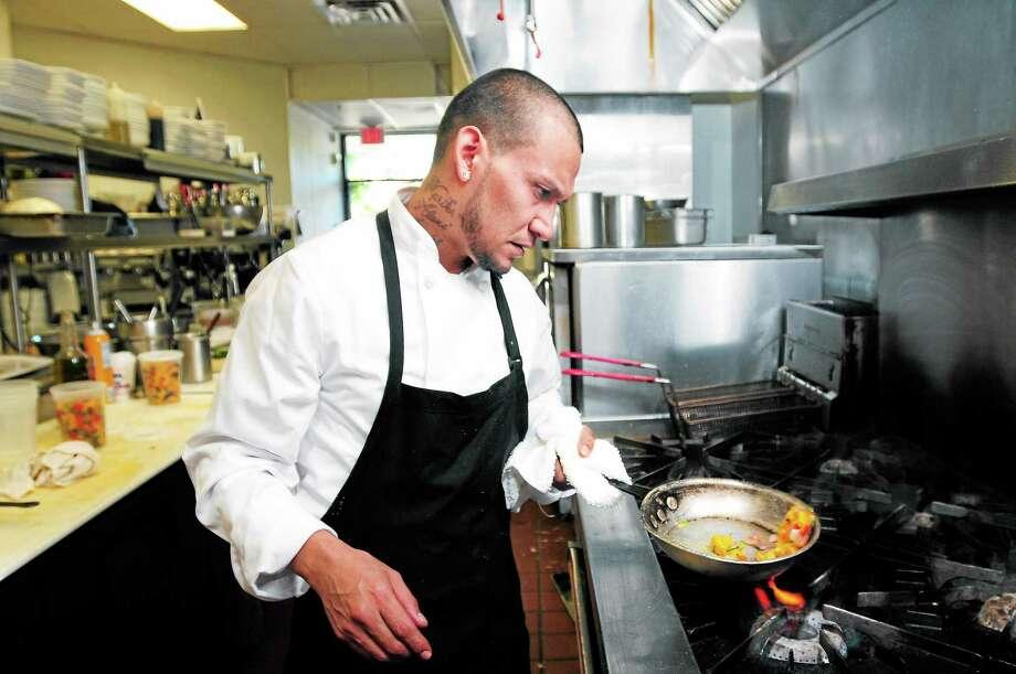 Bin 100 Restaurant head chef Antonio Calderon cooks something in the kitchen. Photo: Arnold Gold — New Haven Register