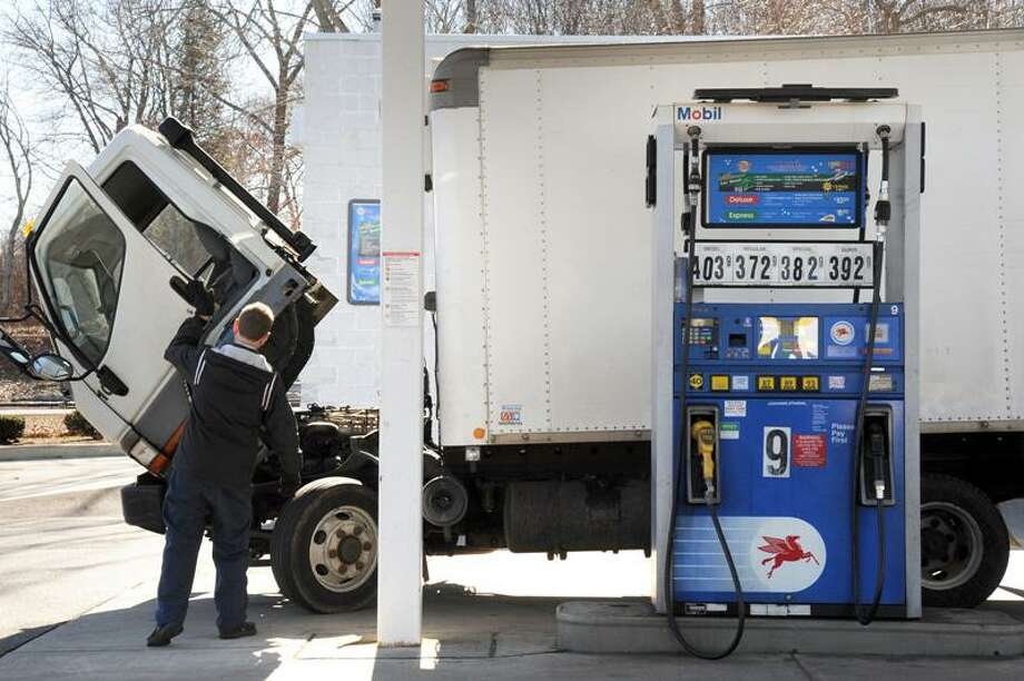 A truck driver fills his tank at Chucky's Mobil on Route 1 in Branford in March 2011. VM Williams/Register file photo