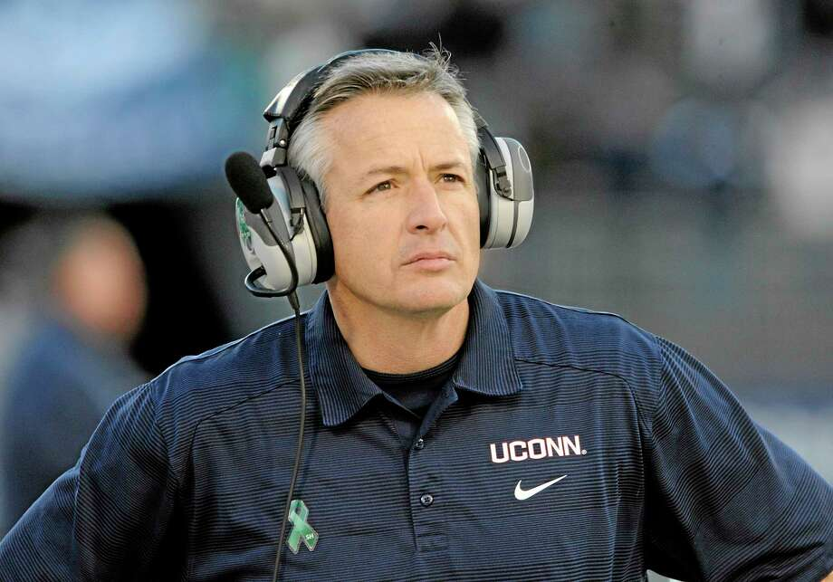 Connecticut head coach T.J. Weist looks at the scoreboard late in his teams' 45-10 victory over Memphis in an NCAA college football game against Memphis in East Hartford, Conn., on Saturday, Dec. 7, 2013. (AP Photo/Fred Beckham) Photo: AP / FR153656 AP