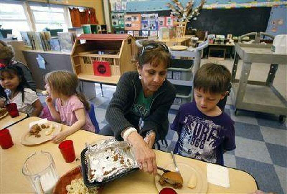 Teacher Diana Feke helps Mason Baker, 5, during lunch at the Eastham Community Center Claskamas County Children's Commission Head Start Monday, April 9, 2012, in Oregon City, Ore. Oregon enrolls relatively few children in its state-funded pre-kindergarten program, but spends more money per student than almost every state, according to an annual report released Tuesday by the National Institute for Early Education. (AP Photo/Rick Bowmer) Photo: ASSOCIATED PRESS / AP2012