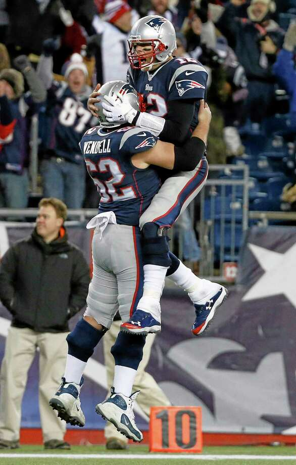 New England Patriots quarterback Tom Brady, right, celebrates his go-ahead touchdown pass with center Ryan Wendell (62) in the fourth quarter of an NFL football game against the Cleveland Browns on Sunday. The Patriots came from behind to win 27-26. Photo: Elise Amendola — The Associated Press   / AP