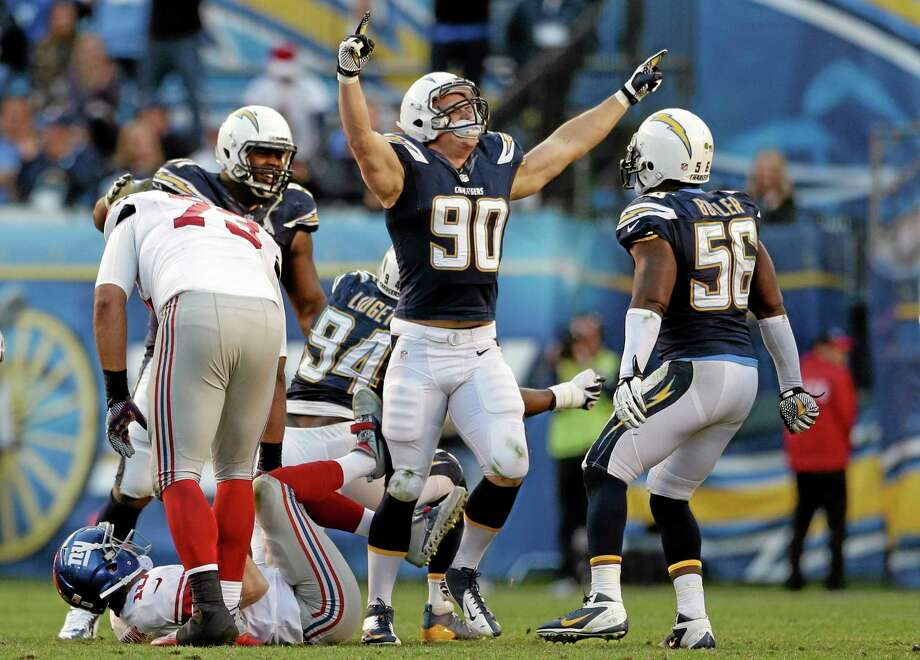 San Diego Chargers linebacker Thomas Keiser (90) celebrates his sack of New York Giants quarterback Eli Manning, bottom left, who is helped back up by teammate James Brewer (73) during an NFL football game on Sunday, Dec. 8, 2013, in San Diego. The Chargers won 37-14. (AP Photo/Gregory Bull) Photo: AP / AP