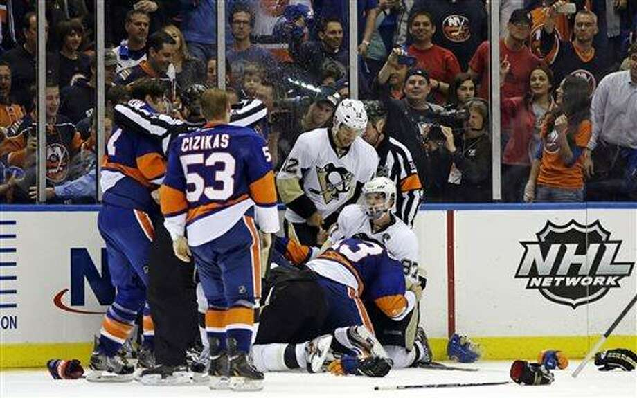 Pittsburgh Penguins right wing Jarome Iginla (12) looks down at center Sidney Crosby (87) during a fight with New York Islanders players at the end of Game 4 of their first-round NHL hockey Stanley Cup playoffs hockey series at Nassau Coliseum in Uniondale, N.Y., Tuesday, May 7, 2013. The Islanders won 6-4. (AP Photo/Kathy Willens) Photo: AP / AP