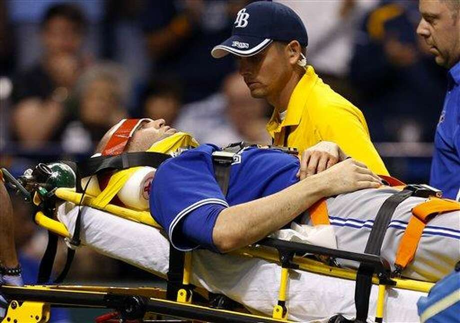 Toronto Blue Jays' J.A. Happ is attended to by medical personnel as he is taken off the field on a stretcher after being hit in the head by a line drive by Tampa Bay Rays' Desmond Jennings during the second inning of a baseball game Tuesday, May 7, 2013, in St. Petersburg, Fla. (AP Photo/Mike Carlson) Photo: AP / FR155492 AP